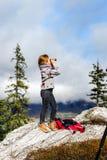 Милая маленькая девочка расследуя горы Альпов используя бинокулярное T Стоковые Фотографии RF