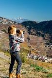 Милая маленькая девочка расследуя горы Альпов используя бинокулярное T Стоковые Фото