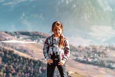 Милая маленькая девочка расследуя горы Альпов используя бинокулярное T Стоковая Фотография RF