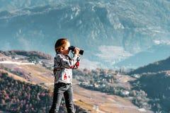 Милая маленькая девочка расследуя горы Альпов используя бинокулярное T Стоковое фото RF