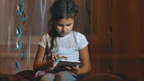 Милая маленькая девочка самостоятельно с планшетом вечером в темной комнате Игра красивой небольшой женской девушки ребенка ребен видеоматериал