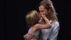 Милая маленькая девочка сидя на ее матерях складывает и целуя ее видеоматериал