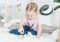 Милая маленькая девочка сидя на кровати и играя доктора со стетоскопом и плюшевым мишкой стоковое фото rf