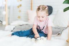 Милая маленькая девочка сидя на кровати и играя доктора со стетоскопом и плюшевым мишкой стоковые фото