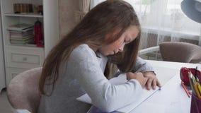 Милая маленькая девочка сидя на таблице и делая домашнюю работу дома видеоматериал