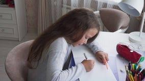 Милая маленькая девочка сидя на таблице и рисуя дома видеоматериал
