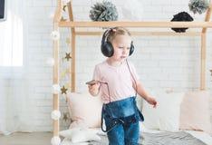 Милая маленькая девочка слушая музыку на наушниках дома стоковая фотография rf