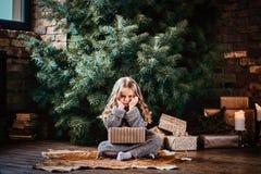 Милая маленькая девочка с белокурым вьющиеся волосы нося теплый свитер держа подарочную коробку пока сидящ на поле рядом с стоковые изображения rf