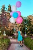 Милая маленькая девочка с большими красочными воздушными шарами идя в парк около городка - изображения стоковая фотография rf