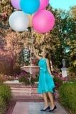 Милая маленькая девочка с большими красочными воздушными шарами идя в парк около городка - изображения стоковые изображения