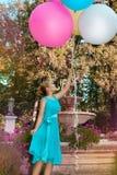 Милая маленькая девочка с большими красочными воздушными шарами идя в парк около городка - изображения стоковое фото rf