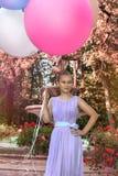 Милая маленькая девочка с большими красочными воздушными шарами идя в парк около городка - изображения стоковые фотографии rf