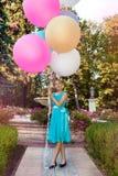 Милая маленькая девочка с большими красочными воздушными шарами идя в парк около городка - изображения стоковое изображение