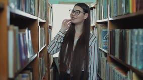 Милая маленькая девочка с длинными черными волосами идет между полками в библиотеке и улыбками сток-видео