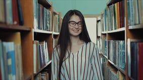 Милая маленькая девочка с длинными черными волосами идет между вертикальными полками в библиотеке и улыбками видеоматериал