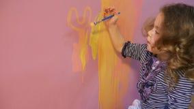 Милая маленькая девочка с курчавыми светлыми волосами рисует на стене акции видеоматериалы