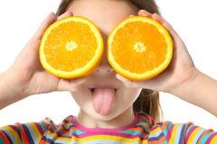 Милая маленькая девочка с половинами апельсина на белой предпосылке Стоковое Изображение