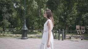 Милая маленькая девочка с солнечными очками длинных волос брюнета нося и длинным белым платьем моды лета идя вниз по улице видеоматериал