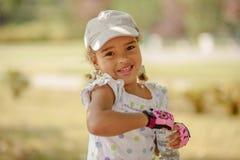 Милая маленькая девочка с темными волосами и коричневыми глазами сидя на траве и смотря в камеру, счастливый и внимательный стоковая фотография