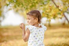 Милая маленькая девочка с темными волосами и коричневыми глазами сидя на траве и смотря в камеру, счастливый и внимательный стоковые изображения