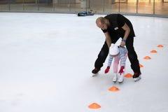 Милая маленькая девочка с тренером изучая фигурное катание стоковое фото