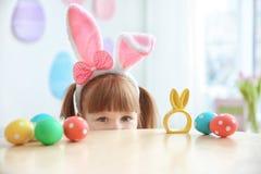 Милая маленькая девочка с ушами зайчика приближает к таблице с пасхальными яйцами Стоковые Фотографии RF