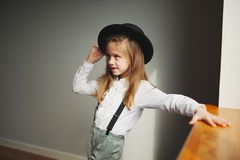 Милая маленькая девочка с черной шляпой дома стоковое фото
