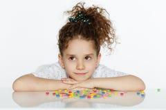 Милая маленькая девочка усаженная на таблицу, положила его подбородок на его руки, смотря сторону одно, изолированную на белой пр стоковая фотография rf