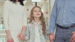 Милая маленькая девочка усмехаясь к камере, держа руки с ее родителями сток-видео