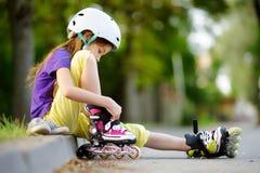 Милая маленькая девочка уча к коньку ролика на красивый летний день в парке стоковая фотография rf