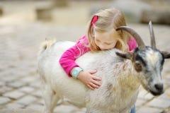 Милая маленькая девочка petting и подавая коза на petting зоопарке Ребенок играя с животноводческой фермой на солнечный летний де Стоковая Фотография