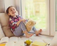 Милая маленькая девушка малыша сидя окном с ее плюшевым медвежонком и смеяться над Стоковое Фото
