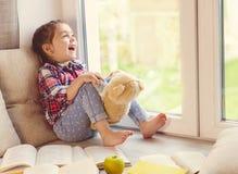 Милая маленькая девушка малыша сидя окном с ее плюшевым медвежонком и смеяться над Стоковые Фото