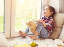 Милая маленькая девушка малыша сидя окном с ее плюшевым медвежонком и смеяться над Стоковая Фотография
