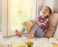 Милая маленькая девушка малыша сидя окном с ее плюшевым медвежонком и смеяться над Стоковые Изображения RF
