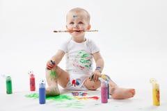 Милая маленькая картина младенца с paintbrush и красочными красками на белой предпосылке Щетка в рте стоковая фотография