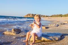 Милая маленькая прелестная девушка малыша в белых одеждах играя с песком и раковинами на пустом пляже на теплый солнечный летний  Стоковые Фотографии RF