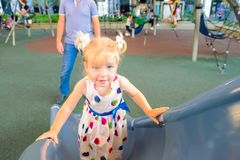 Милая маленькая усмехаясь blondy девушка малыша в платье взбираясь на холме ` s детей на momern спортивной площадке лета с ее отц Стоковая Фотография RF