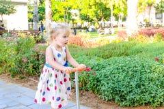 Милая маленькая эмоциональная удивленная blondy девушка малыша в самокате катания платья в рекреационной зоне парка города Активн Стоковая Фотография RF