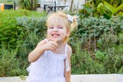 Милая маленькая эмоциональная blondy девушка малыша в платье есть ручку закуски моркови во время прогулки в парке города Еда здор Стоковые Фото