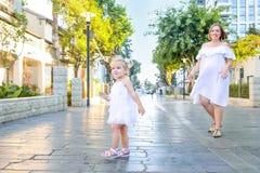 Милая маленькая эмоциональная blondy девушка малыша в платье при беременная мать играя, заразительные пузыри мыла во время прогул Стоковые Фотографии RF