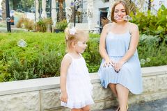 Милая маленькая эмоциональная blondy девушка малыша в платье при беременная мать играя, заразительные пузыри мыла во время прогул Стоковые Фото