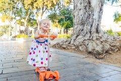 Милая маленькая эмоциональная blondy девушка малыша в платье смотря камеру и ехать самокат в рекреационной зоне парка города с bu Стоковое Изображение RF