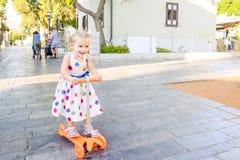 Милая маленькая эмоциональная blondy девушка малыша в самокате катания платья в рекреационной зоне парка города с зданиями и дере Стоковое фото RF