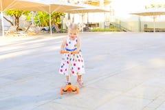 Милая маленькая blondy девушка малыша в самокате катания платья в рекреационной зоне парка города с сенью, зонтиками Активный отд Стоковое Изображение RF