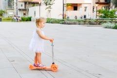 Милая маленькая blondy девушка малыша в самокате катания платья в рекреационной зоне парка города с сенью, зонтиками Активный отд Стоковая Фотография