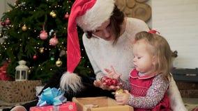 Милая мама женщины сидит на поле в праздничной студии и играх с небольшим ребенком в одеждах стильного плюша красных близко акции видеоматериалы