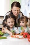 Милая мать и ее дети делая vegetable салат Стоковое Изображение