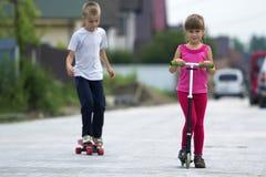 Милая молодая белокурая девушка детей в розовой одежде на самокате и красивом мальчике на скейтборде играя на солнечной улице на  стоковая фотография