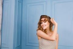 Милая молодая белокурая девушка с играми вьющиеся волосы с ее волосами Платье и стойки света Shewears в студии с голубыми стенами стоковая фотография